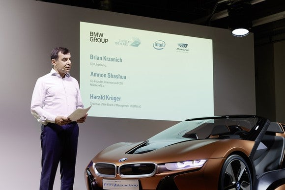 Amnon Shashua is shown standing on a stage next to a brown BMW i8 sports car.