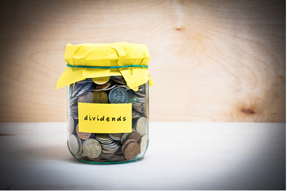 "A jar with a yellow label with the word ""dividend"" on it, filled with change."