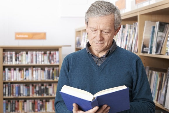 Senior man reading a book in a library