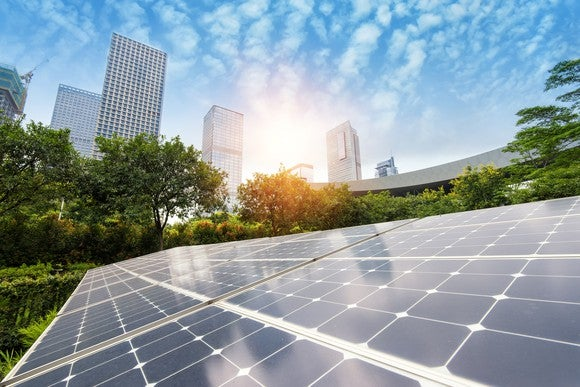 Solar panels with a city skyline in the background.