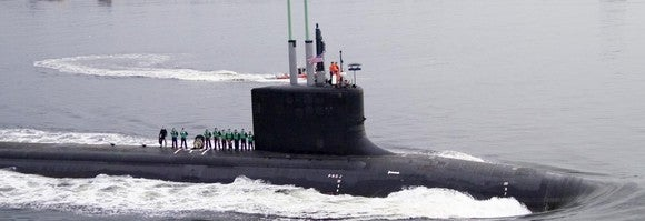 Nuclear submarine in the water, with a crew standing on deck.