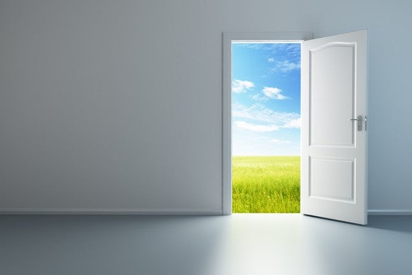 Open door with blue sky and a field behind