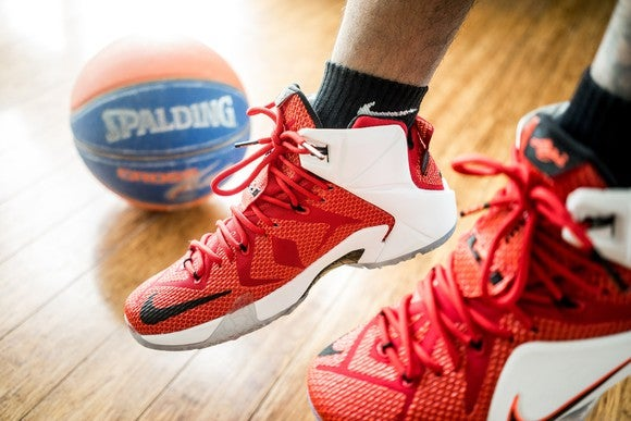 Basketball player's feet with Nike shoes and a basketball in the background.