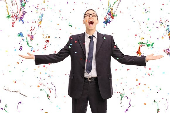 Business man with confetti falling around him, excited look on his face.