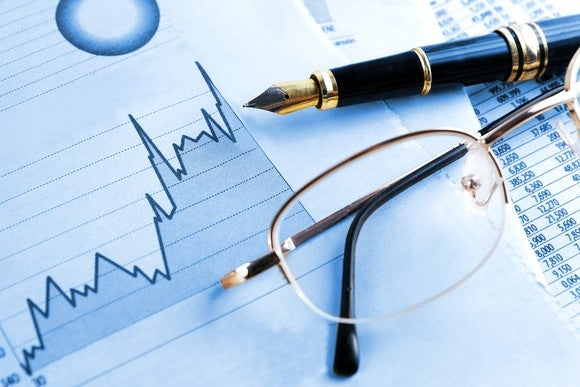 Rising stock chart, pen, and eyeglasses
