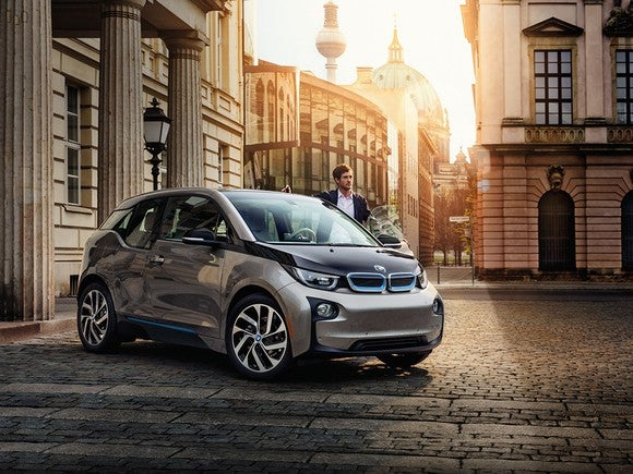 BMW i3 parked on cobblestone road at dusk