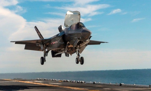 F-35B fighter jet hovering over aircraft carrier deck.