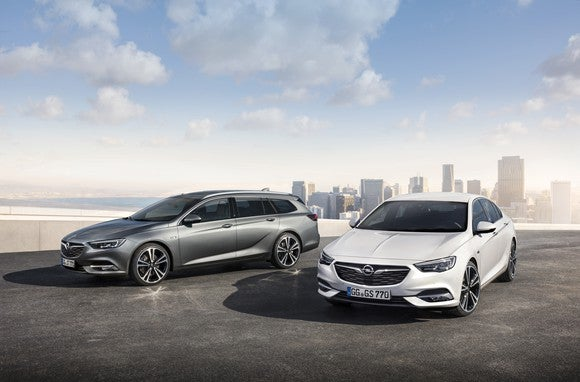 Two 2018 Opel Insignias, a wagon and a 5-door, are shown with a city in the background.