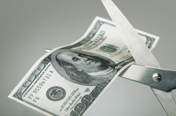 Scissors cutting a $100 bill in half