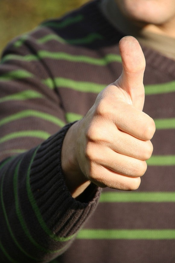 Torso of someone in sweater, giving thumbs-up