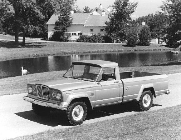 A black and white photo of a 1968 Jeep Gladiator pickup truck in a farm setting.