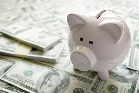 A white piggy bank sits on top of a pile of money.