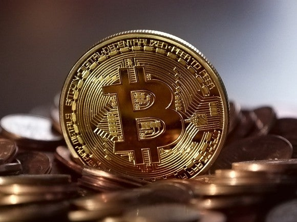 A bitcoin sitting on top of other gold coins