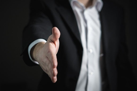 Business man extending arm to offer a hand shake