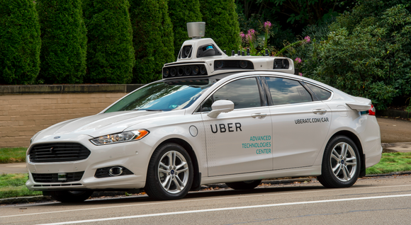 A white Ford Fusion sedan equipped with Uber's self-driving sensors.