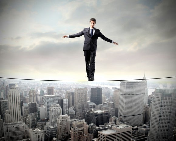 A businessman walks a high wire between two buildings.