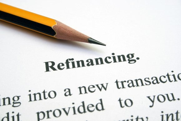 "Part of a paper is visible, on which is written ""refinancing,"" Part of a pencil is shown, too."