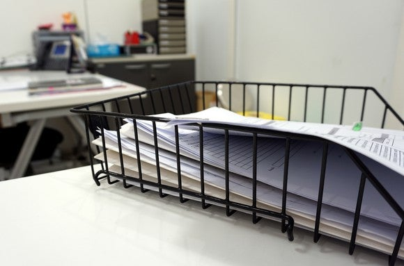 A pile of documents in a wire basket on a desk.