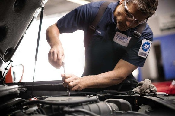 Mechanic working on vehicle at a Sears Auto Center.