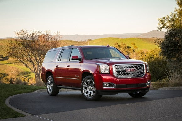 A red 2017 GMC Yukon Denali XL SUV in a sunlit country setting.