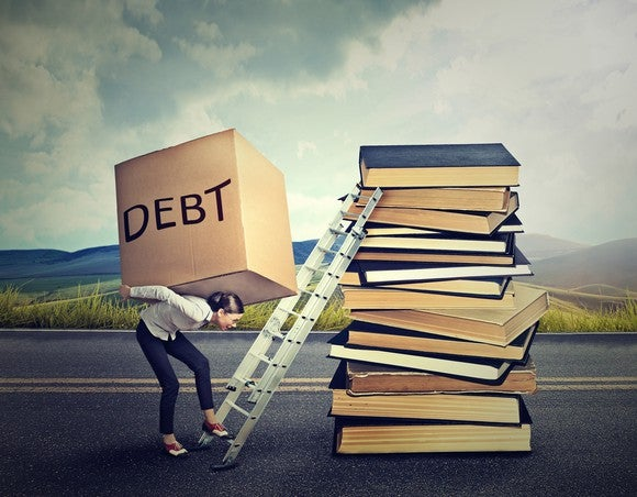 A person carries a box labeled debt up a ladder.