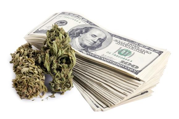 A marijuana bud next to a stack of hundred dollar bills.