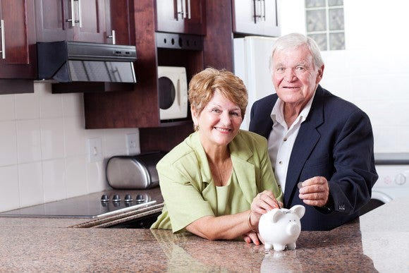 An older couple in a kitchen with a piggy bank.