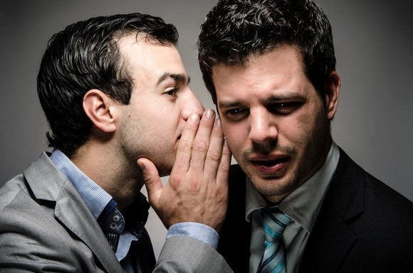 Businessman whispering in the ear of another businessman