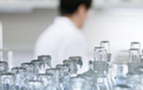 A lab worker prepares bottles containing marijuana-based medicines.