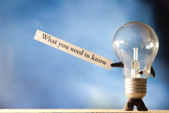 """Light bulb holding strip of paper on which is written """"what you need to know"""""""