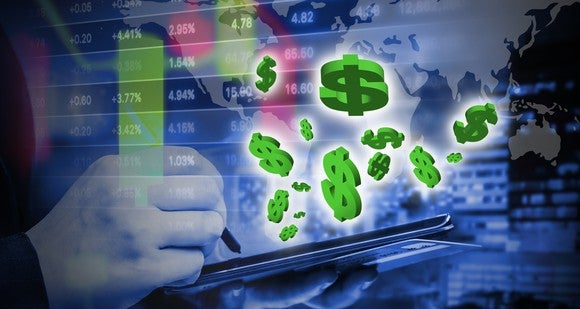 Jumbly graphic of blue computer screen with stock listings, dollar signs flying toward viewer, and a hand writing on a tablet