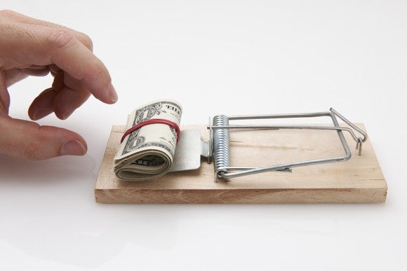 Money in a mousetrap, with a hand approaching.