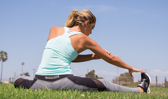 Female athlete stretching clothed in Skechers exercise gear.