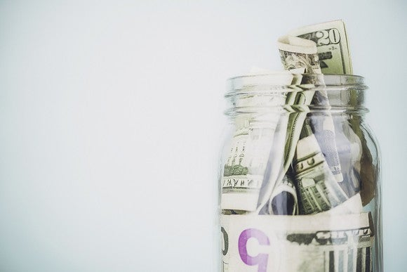 Dollar bills of different denominations stuffed into a jar.