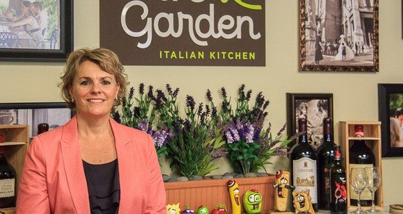 A woman standing behind the counter at Olive Garden.