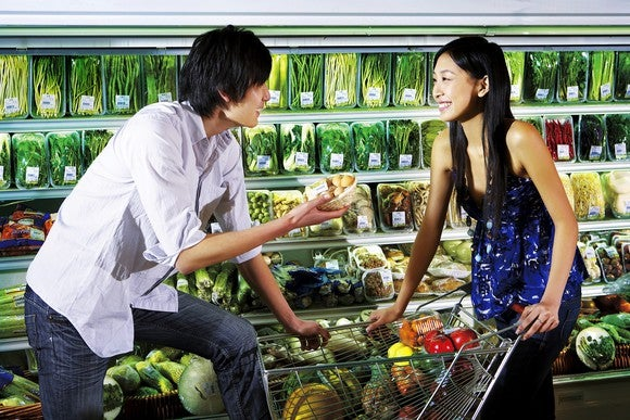 Asian man and woman talking to each other in a supermarket
