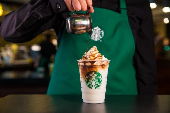 A Starbucks' employee putting the finishing touches on a  frozen drink