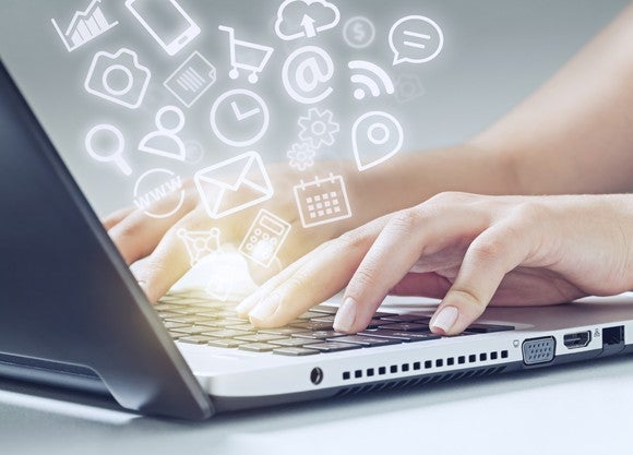 """A woman types on a laptop keyboard, and a cloud of icons """"floats"""" out."""
