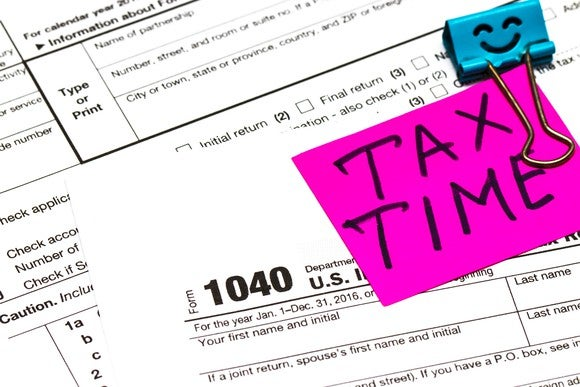 "Part of tax forms visible, with pink note clipped to them, that says ""Tax Time"""