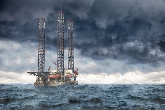 Oil rig at sea under stormy skies.
