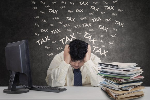 """Man at desk with head in hands, near pile of folders, with the word """"tax"""" written many times on a blackboard behind him."""