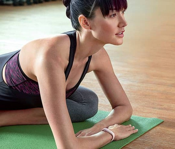 Woman performing yoga wearing a Fitbit Alta with leather band