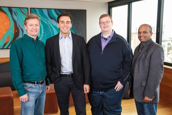 The four men are standing in a conference room.