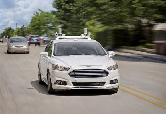 A white Ford Fusion with self-driving sensors on a suburban street.