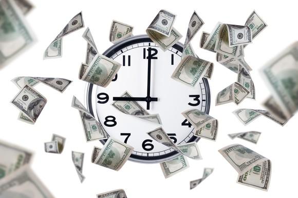Clock with dollar bills around it.