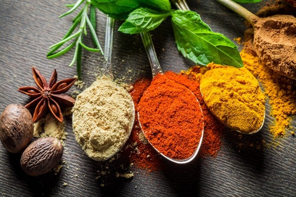 Four spoons filled with colorful spices.