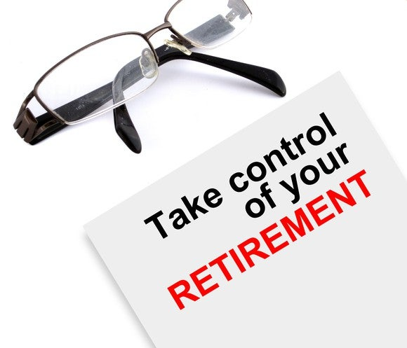 "Sign that says ""take control of your retirement"" next to a pair of glasses."