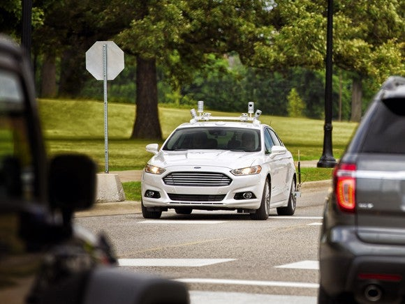 A white Ford Fusion with visible self-driving sensors is shown on a suburban street.