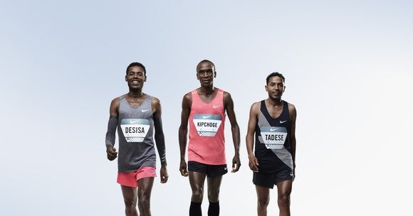 Three runners walk side by side wearing Nike's tech advanced running gear. In the group might be the first (or first three) people to ever run a marathon in under 2 hours.