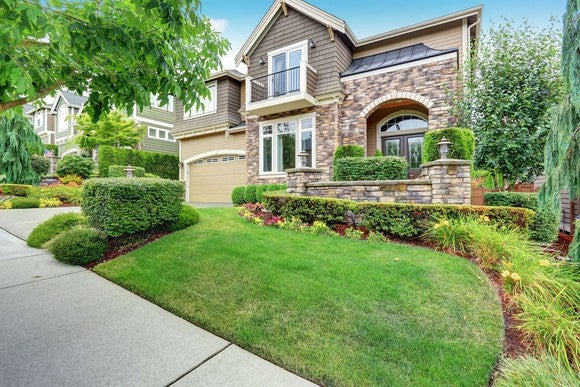Beautiful new home with manicured front lawn and garden